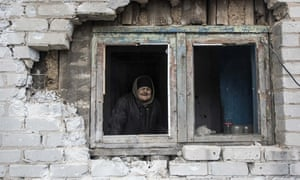 An elderly woman looks through the window in her house damaged by shelling in Avdiivka, eastern Ukraine.