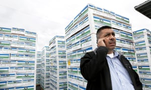 In this 5 November 2014, file photo, Saul Ruiz talks on the phone to learn whether or not to continue loading apples into a semi-trailer at the Apple King warehouse in Gleed, Washington.