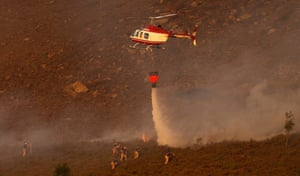A helicopter drops water as firefighters tackle the blaze
