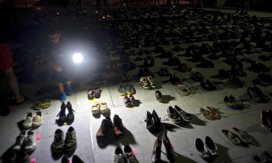A child shines a light on hundreds of shoes at a memorial for those killed by Hurricane Maria, in front of the Puerto Rico Capitol in San Juan on 1 June 2018.