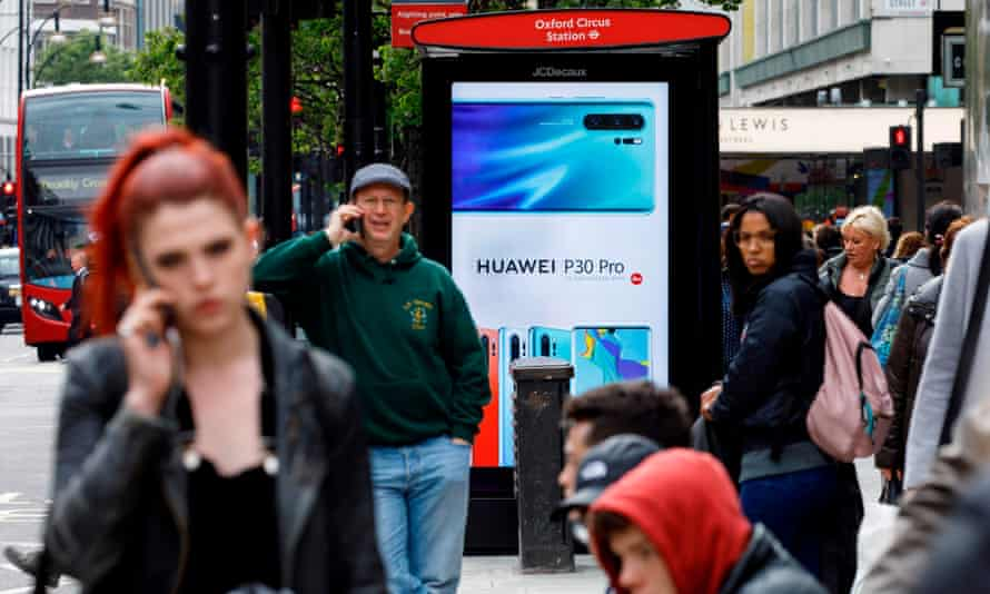 Huawei advert on a bus stop in a busy London street