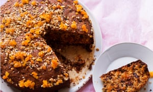 A chocolate cake with pieces of apricot on top, and a slice taken from it on a plate