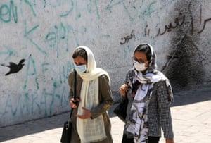 Women wearing face masks walk down a street in Tehran on Sunday.