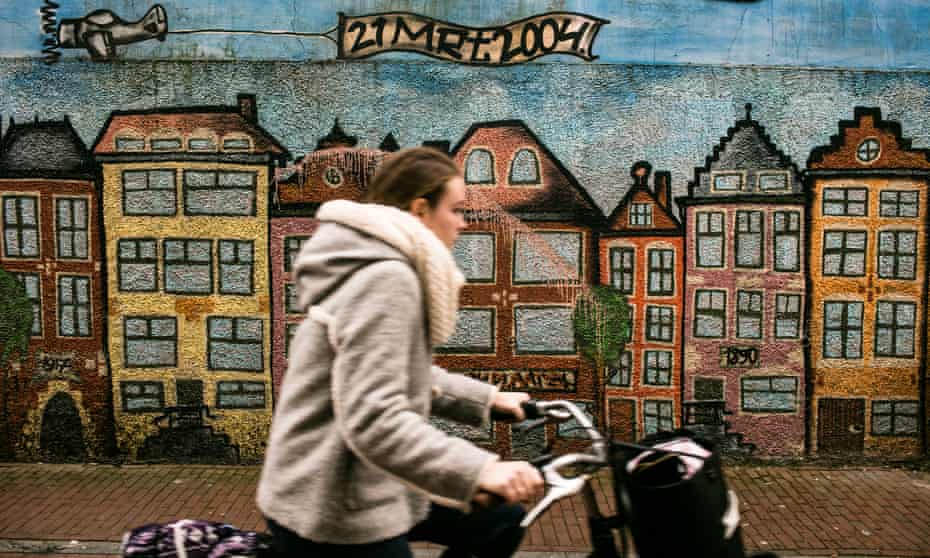 A cyclist passes a painted wall in Leeuwarden city centre