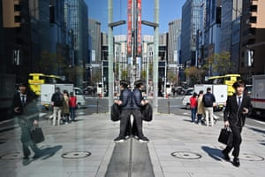 Tokyo, Japan. A businessman runs down the pavement in the city's Ginza district