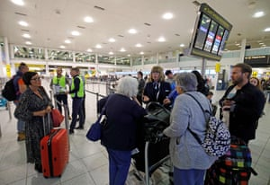 Officials talk with passengers at the Thomas Cook Check-In desks at the South Terminal of London Gatwick Airpor.