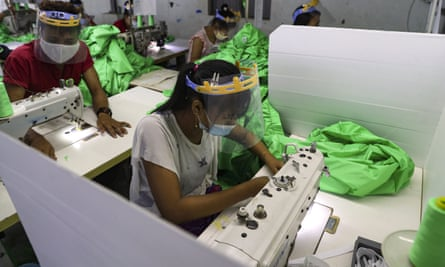 Garment workers in Myanmar work wearing face mask and shields to help curb the spread of Covid-19.