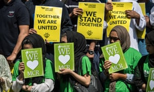 "Men and women from the East London Mosque holding up placards saying ""We stand together"" after the Manchester attack"