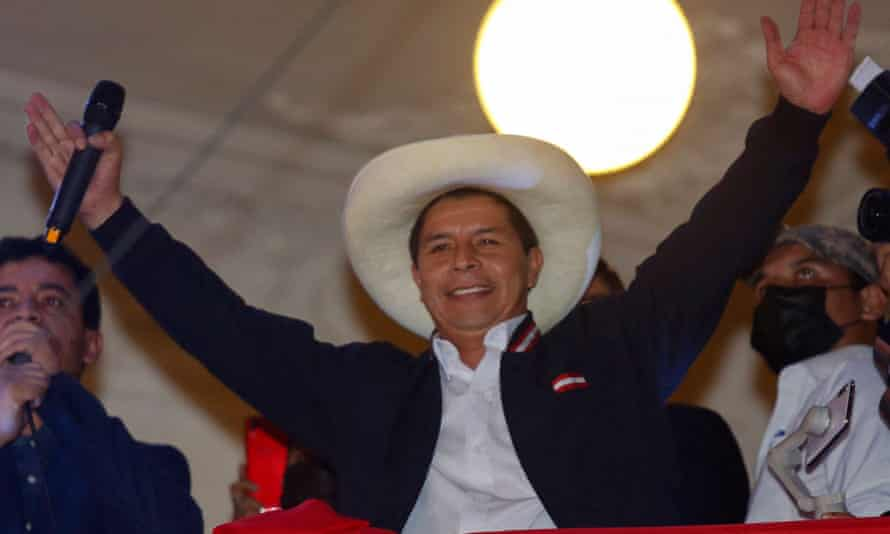 Former school teacher Pedro Castillo raises his arms from the balcony of the Peru Libre party headquarters in Lima, following the official proclamation of him as Perus president-elect.