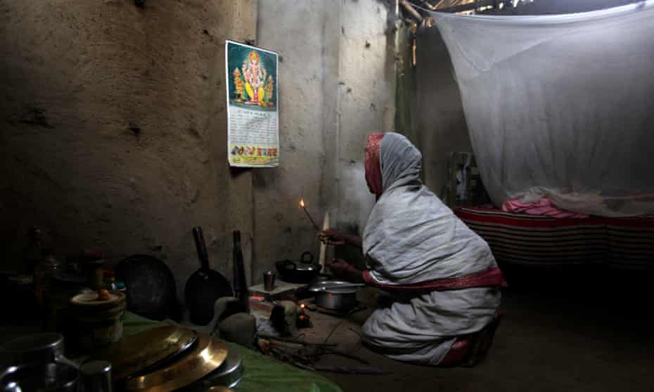 An Assam woman prays before a picture of the Hindu god Ganesha.