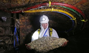 A sewer worker holding a fatberg