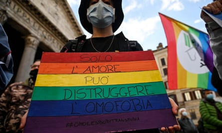 A protester in Rome carries an LGBT pride placard reading 'only love can destroy homophobia'.