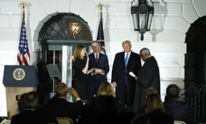 Donald Trump stands with supreme court justice Clarence Thomas as he swears in Amy Coney Barrett. Her husband Jesse Barrett stands with her.