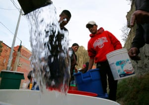 Neighbours get water from a water truck in Kupini, La Paz