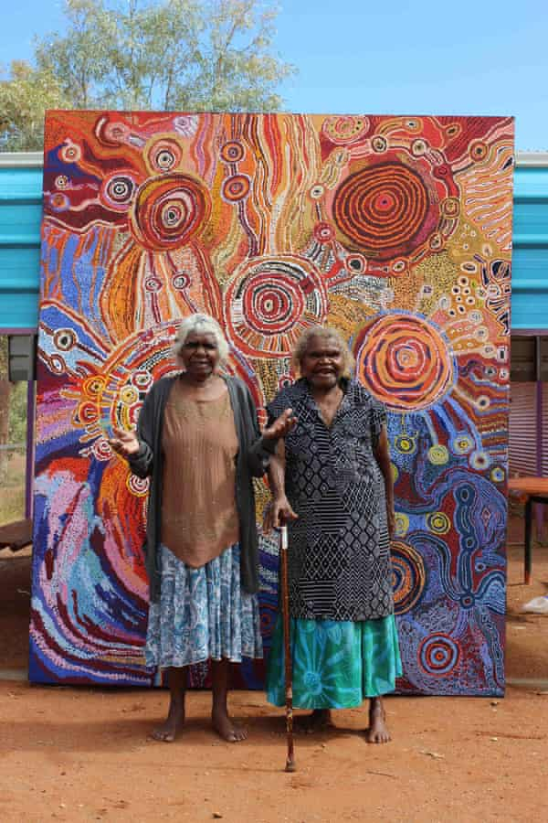 APY senior female artists Paniny Mick and Wawiriya Burton in front of a painting of the seven sisters story – the largest piece to be auctioned to raise funds for the Purple House dialysis clinics