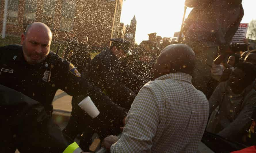 Demonstrators and police officers wrestle over a metal barricade as containers of liquid are thrown during a protest following the death of Freddie Gray.