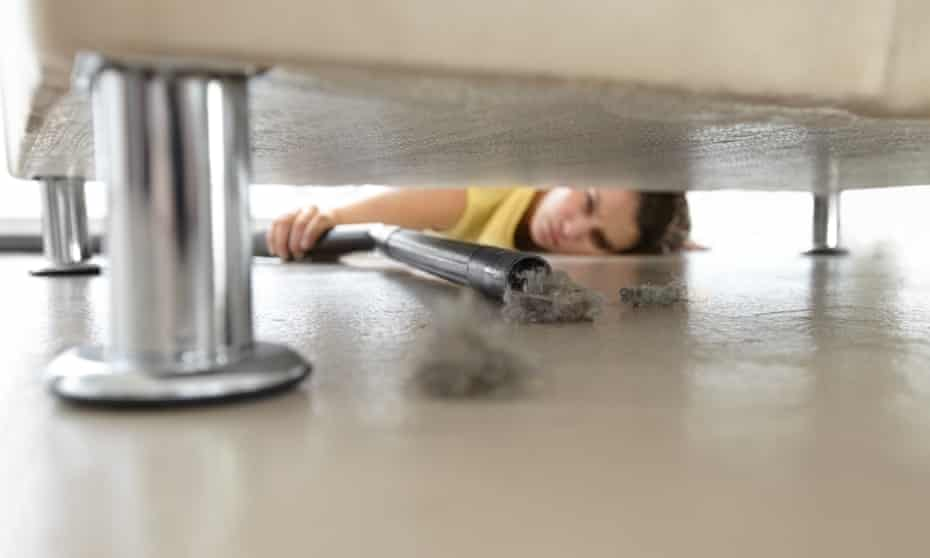 A woman reaching under a sofa to vacuum some dust