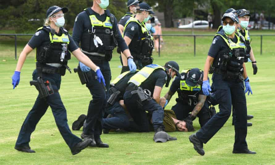 Police arrest protesters during an anti-vaccination rally in Melbourne, Victoria. The national rollout of the Pfizer vaccine will begin on Monday