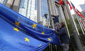 Workers adjust a European flag outside the EU parliament in Brussels
