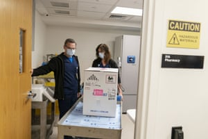 Pharmacists Richard Emery, left, and Karen Nolan, wheel a box containing the Pfizer-BioNTech vaccine as it arrives at Rhode Island Hospital in Providence.