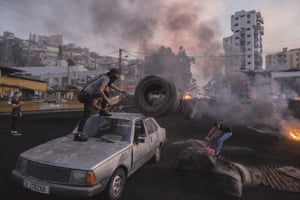 Protesters unload tyres from a car to block a highway in Beirut during the unrest sparked by the economic difficulties.