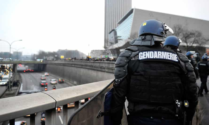 French gendarmes monitor the taxi drivers' protest from a bridge in Paris on Tuesday.