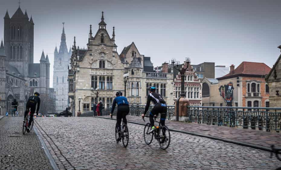 Wiggins, on the left, cycling through Ghent, the city he was born in