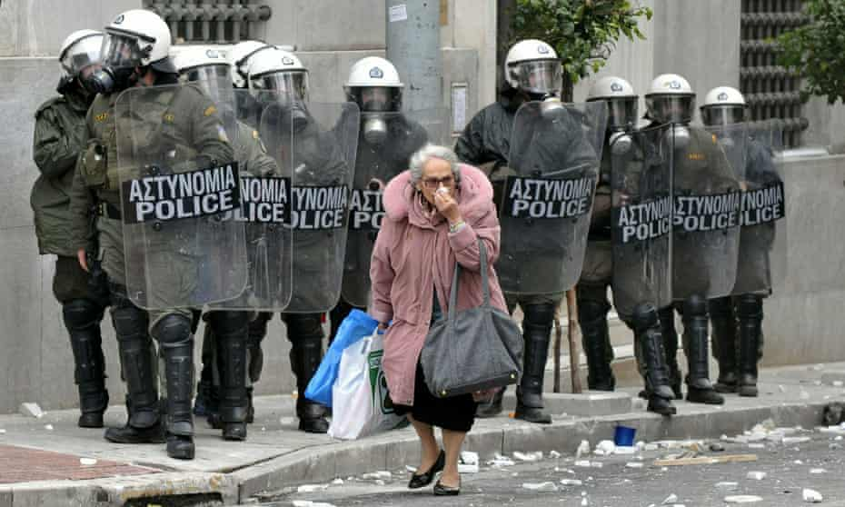 A woman walks past riot police during clashes with protestors December 15, 2010 in Athens, Greece.