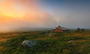 Alpine  landscape with dramatic sky and old stone cabin.