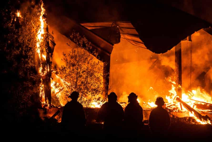 Firefighters look on as a structure burns during the Kincade fire off Highway 128, east of Healdsburg, California, on Tuesday..