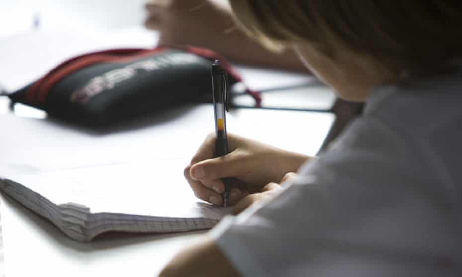 Child writing in exercise book at chool