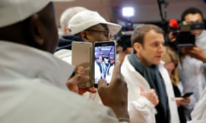 Butchers at the meat pavilion in Rungis international food market take photos of French presidential hopeful Emmanuel Macron on Tuesday.
