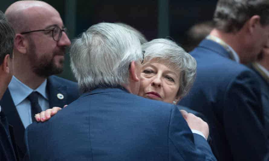 Theresa May being embraced by Jean-Claude Juncker
