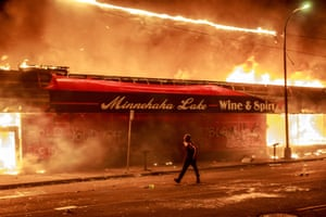 A man walks past a liquor store in flames near the Third Police Precinct