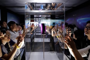 Visitors look at Xiaomi MIX Alpha smartphones after the launch of a new 5G smartphone