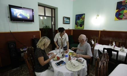 Tourists eat at a <em>paladar</em> or home restaurant in the town of Cienfuegos.