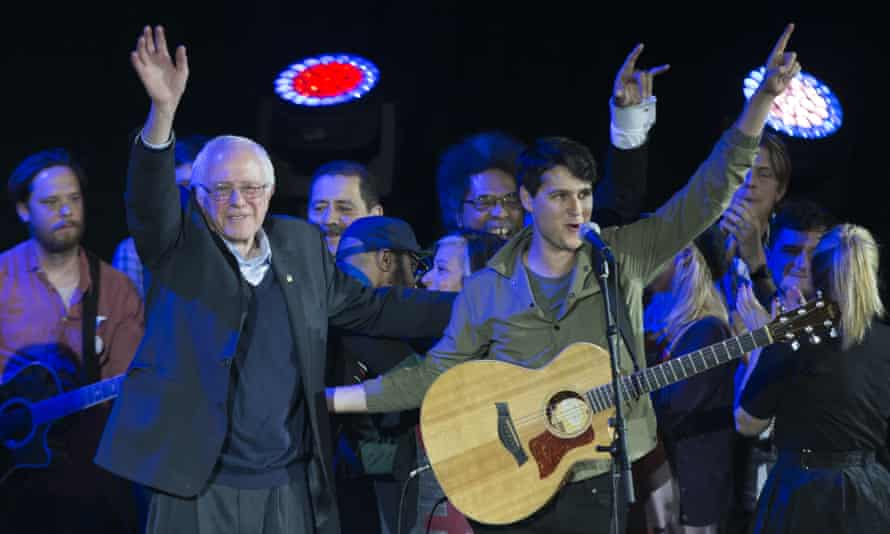 Bernie Sanders with Vampire Weekend lead singer Ezra Koenig wave during a campaign rally.