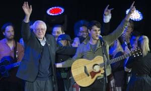 Bernie Sanders and Vampire Weekend lead singer Ezra Koenig wave during a campaign rally at the University of Iowa.