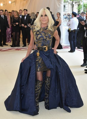 Designer and another of the Met Gala 2018 co-chairs Donatella Versace wears one of her own designs, an embroidered navy and gold mini-dress topped with a sweeping navy overskirt