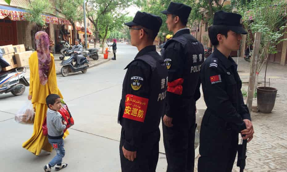 Police patrol the Old Town in Kashgar, to the west of Luopu county.