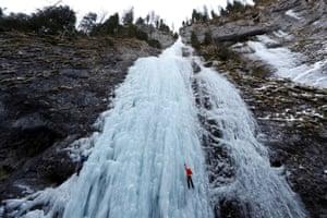 An Italian alpine rescuer climbs a frozen waterfall in Malga Ciapela.
