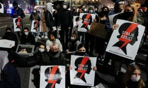 Demonstrators holding 'women's strike' placards block a street in Warsaw during a protest over the constitutional tribunal's abortion ruling.