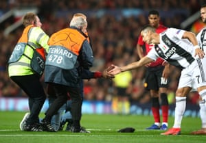 Stewards apprehend a pitch invader as Ronaldo shakes his hand.