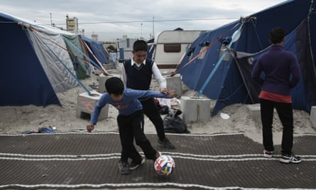 boys play football in the Calais refugee camp