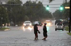 Two men wade across 19th Street in Galveston, Texas, Wednesday.
