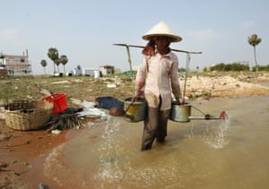 A farmer carries pots loaded with water for watering her vegetable crops outside Phnom Penh, Cambodi