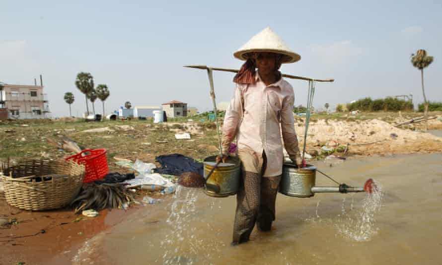 A farmer carries pots loaded with water from a pond for watering her vegetable crops. Tens of millions of people in the region are affected by the low level of the Mekong, a rice bowl-sustaining river system that flows into Laos, Thailand, Cambodia and Vietnam.