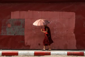 Yangon, Myanmar: A Buddhist monk uses an umbrella to protect himself from the sun