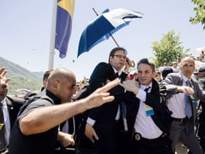 Bodyguards try to protect Serbian Prime Minister Aleksandar Vučić  from stones hurled at him by an angry crowd at the Srebrenica-Potocari Memorial Centre