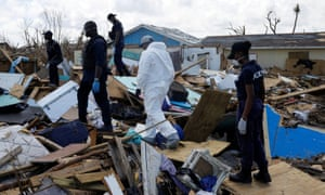 Police officers search for the dead in the destroyed Mudd neighborhood after Hurricane Dorian hit the Abaco Islands in Marsh Harbour, Bahamas, on 10 September.